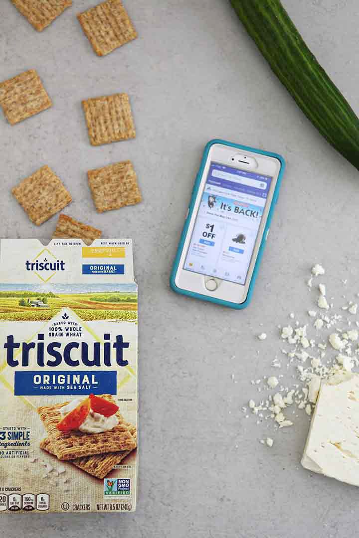Ingredients for the cucumber bites are shown on a grey background, including TRISCUIT Crackers, crumbled feta cheese, an English cucumber and shown next to a mobile phone showing the Albertsons app