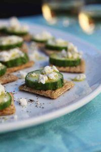 TRISCUIT Cucumber Bites are served on a white platter with white wine in the background