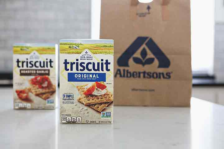 Two boxes of TRISCUIT Crackers stand in front of an Albertsons bag on a kitchen counter