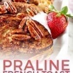 A close up of Praline French Toast with a fresh strawberry and Pinterest text