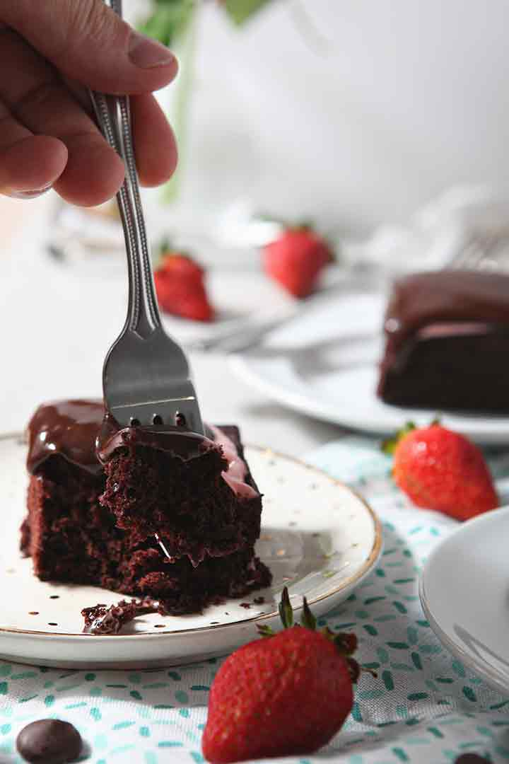 A fork cuts into a slice of Strawberry Chocolate Cake