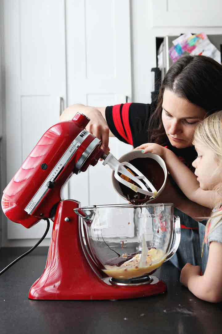 A woman and a girl pour melted chocolate into the bowl of a stand mixer