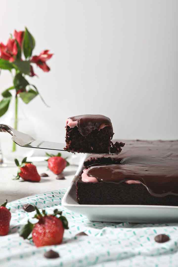 A slice of Strawberry Chocolate Cake is lifted out of the cake