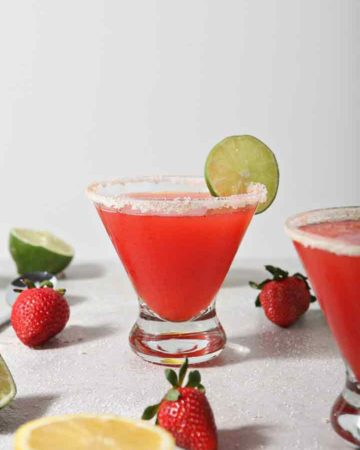 Close up of two Strawberry Margaritas, surrounded by fresh fruit
