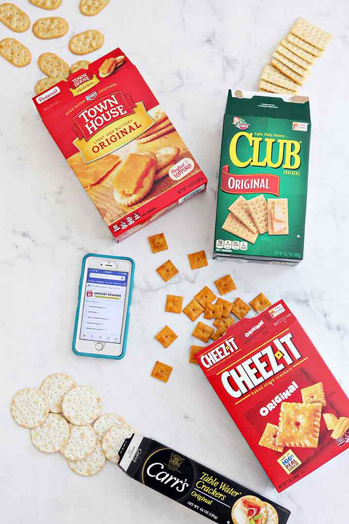Crackers spill out of their boxes and are shown with a phone displaying the Albertsons app