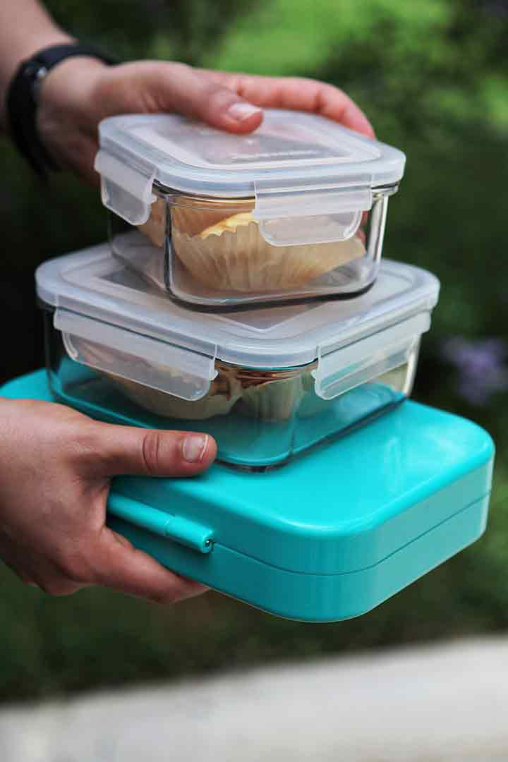 A man holds three food storage containers of cracker sandwiches to be taken to a picnic