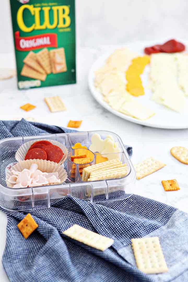 A make-your-own cracker snack kit is shown with several meats and cheese and a Club cracker box behind it