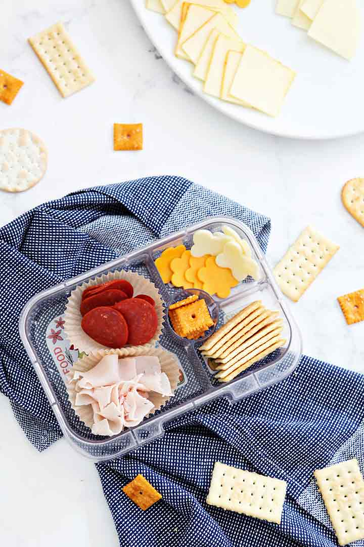 A make-your-own cracker snack kit is shown from above with several meats and cheese