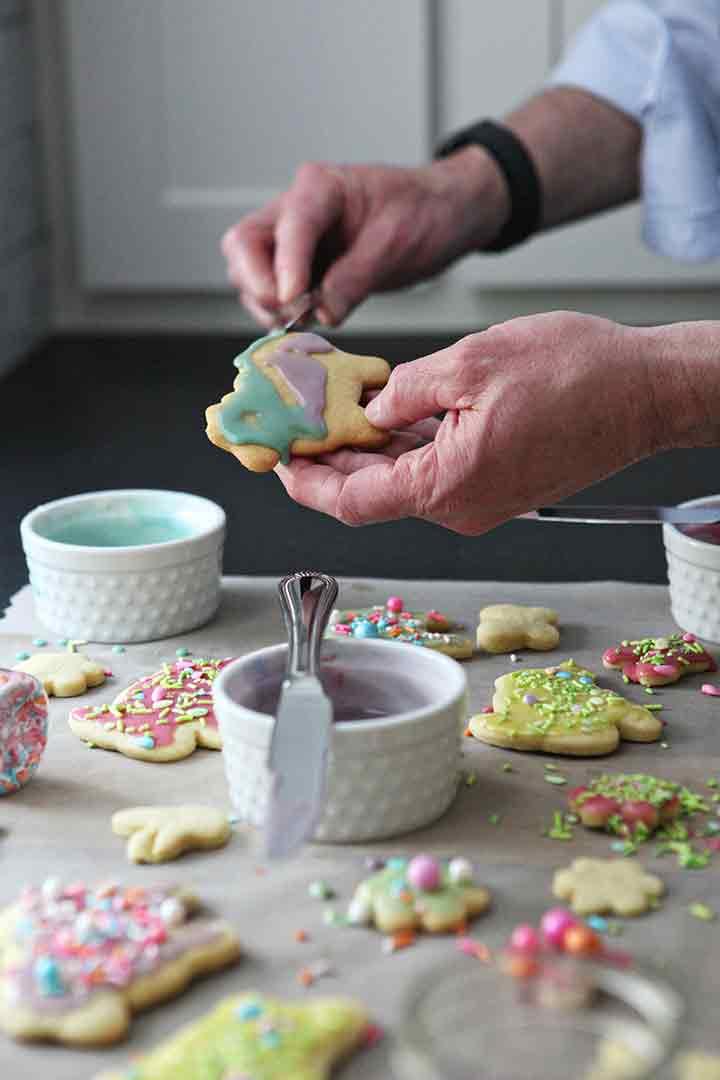 A man drizzles colorful Lemon Icing onto a Lemon Tea Cake Cookie