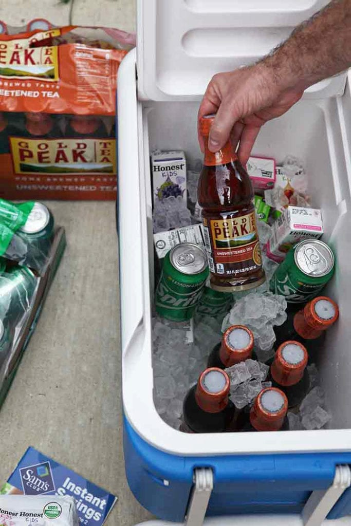 A man places drinks in a cooler to chill before an outdoor entertaining event