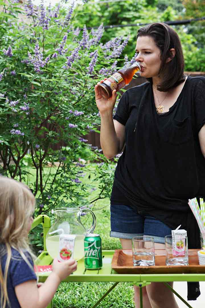 A woman and a child enjoy drinks at an homemade outdoor drink station