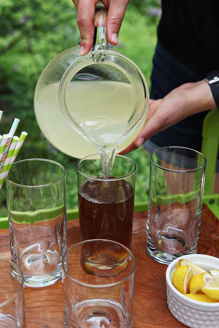 A woman pours lemonade on top of tea in a glass while entertaining outdoors