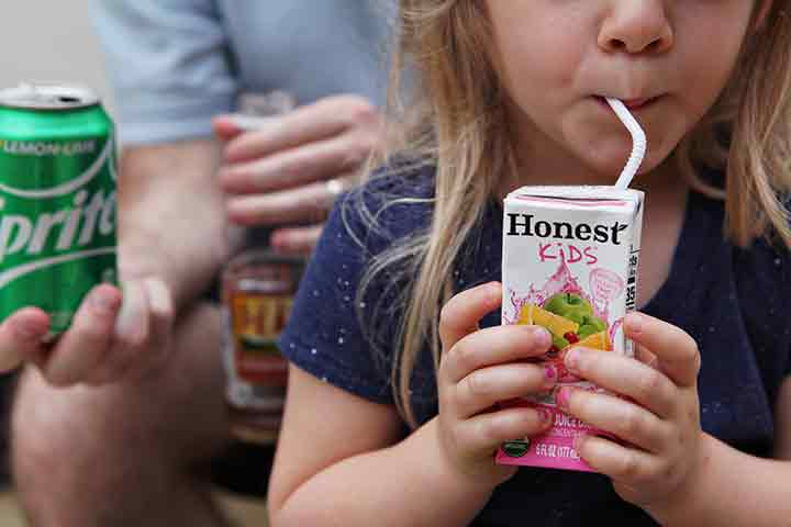 A girl drinks an Honest Kids juice box while a man sits behind her with a Sprite and a Gold Peak tea