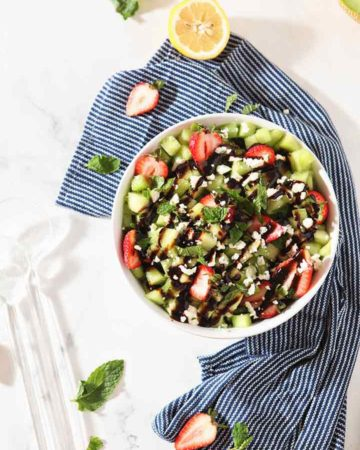 Overhead image of the final Strawberry Melon Salad in a white bowl with a blue napkin