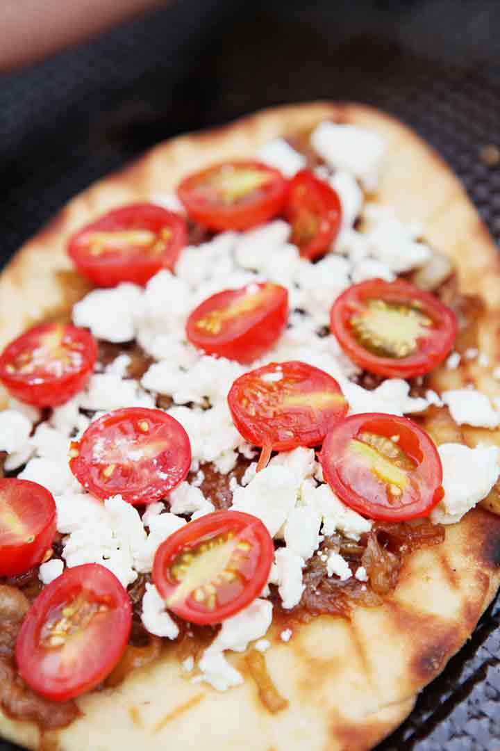 This grilled flatbread pizza recipe is shown on a baking sheet after coming off the grill