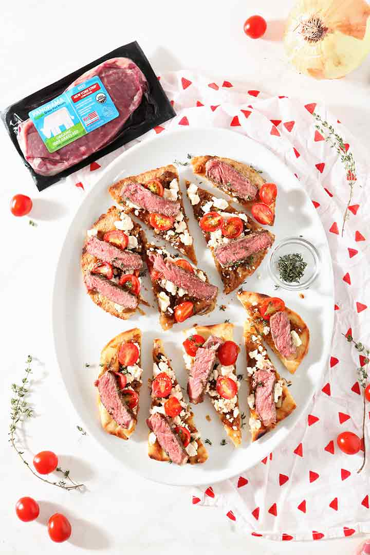 Two Grilled Steak Flatbread Pizzas are shown on a tablescape with a package of Panorama NY Strip Steak