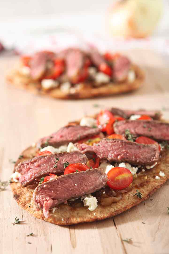 Close up of a grilled steak flatbread pizza recipe on a wooden cutting board