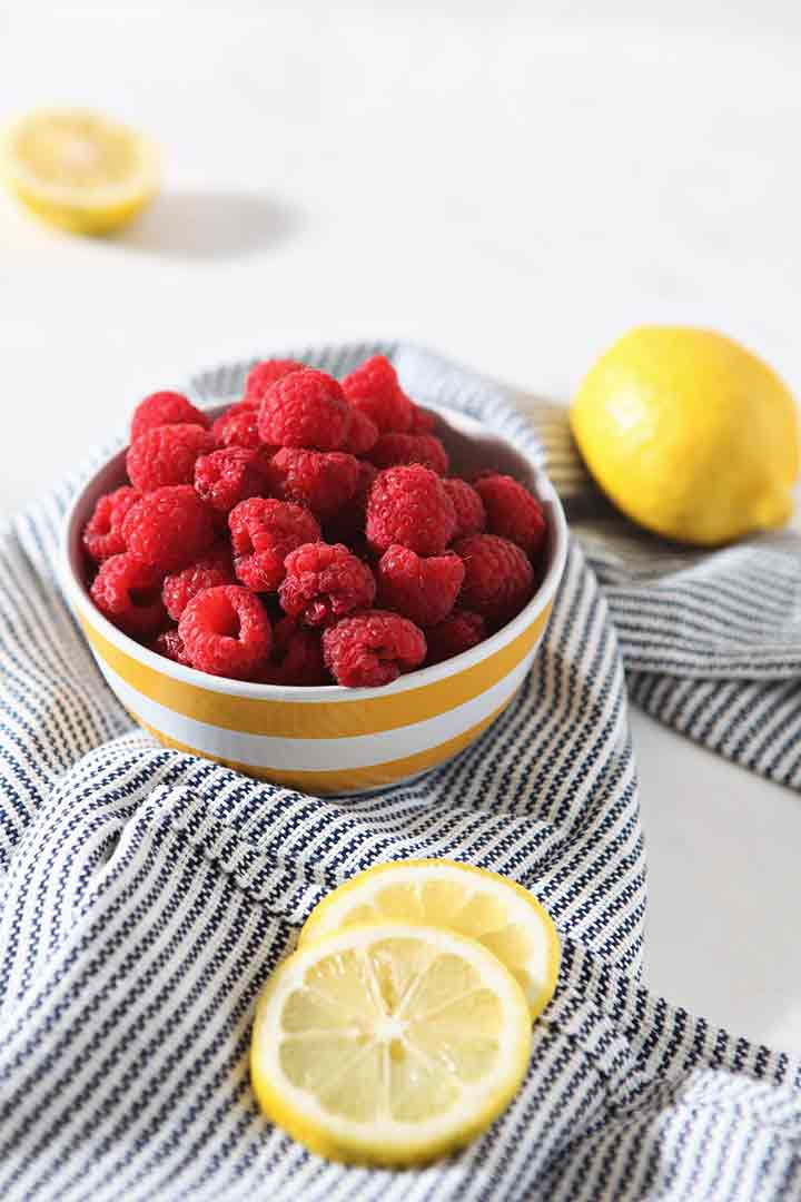 A bowl of raspberries is shown with whole and sliced lemons