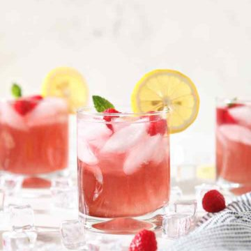 Three glasses of Spiked Raspberry Lemonade are surrounded by ice, raspberries and lemons