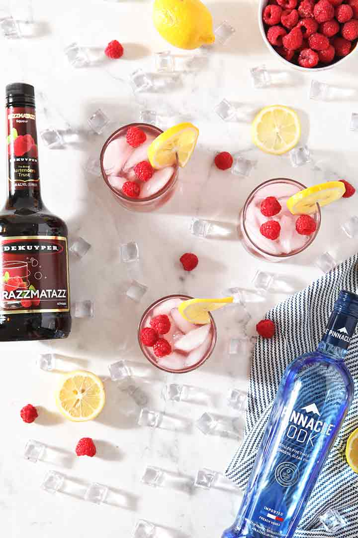 Vodka Lemonades with Raspberry from above, with the bottles of alcohol, and ice