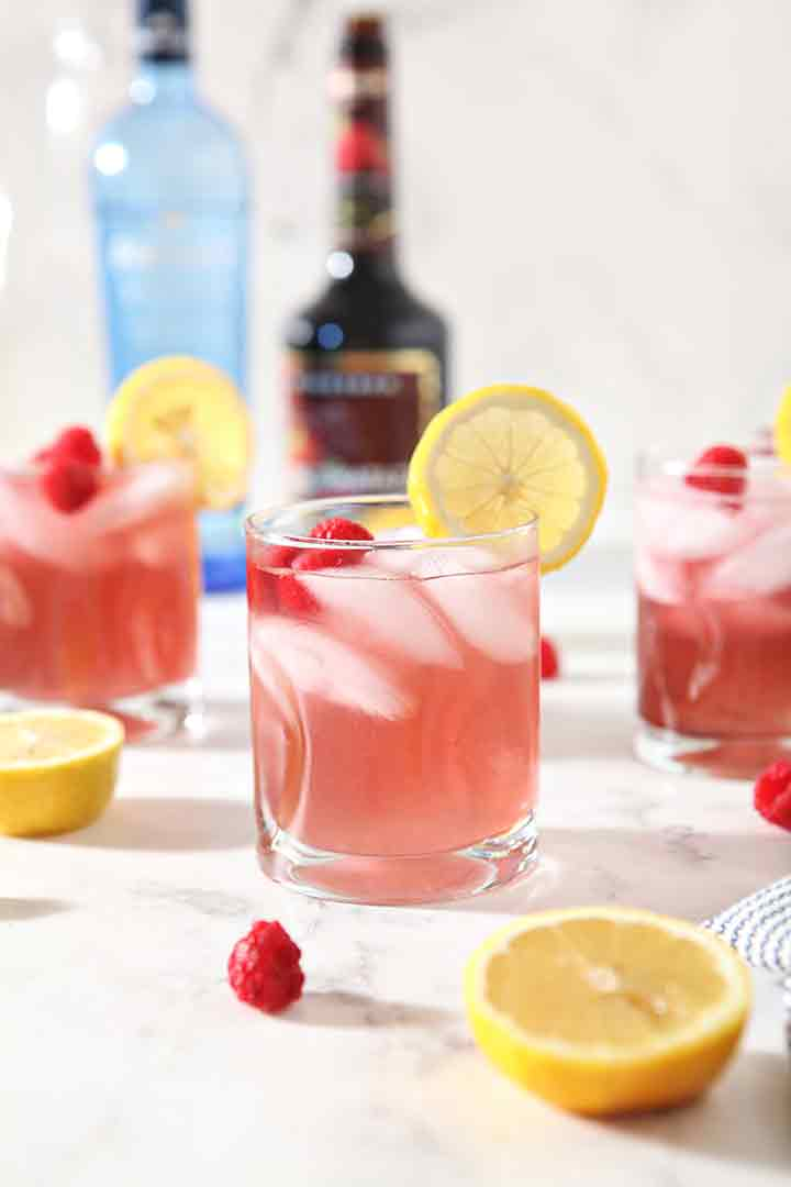 Three Vodka Lemonades with Raspberry are shown, garnished and surrounded by fresh fruit and the ingredients