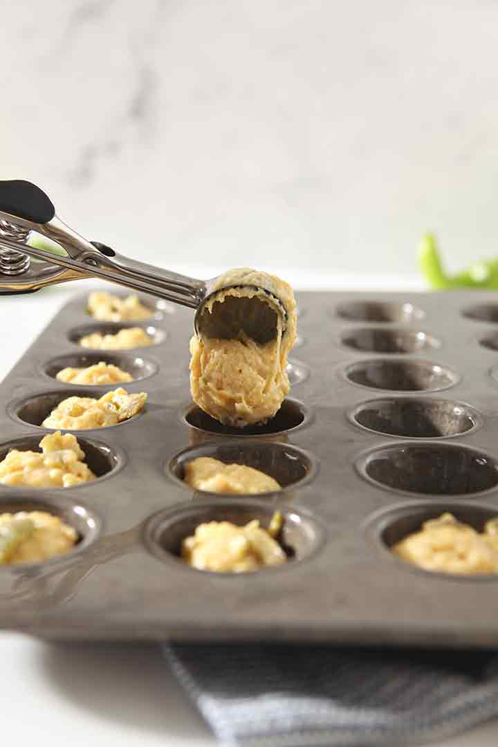 A cookie scoop is used to scoop the dough into the prepared mini muffin tin