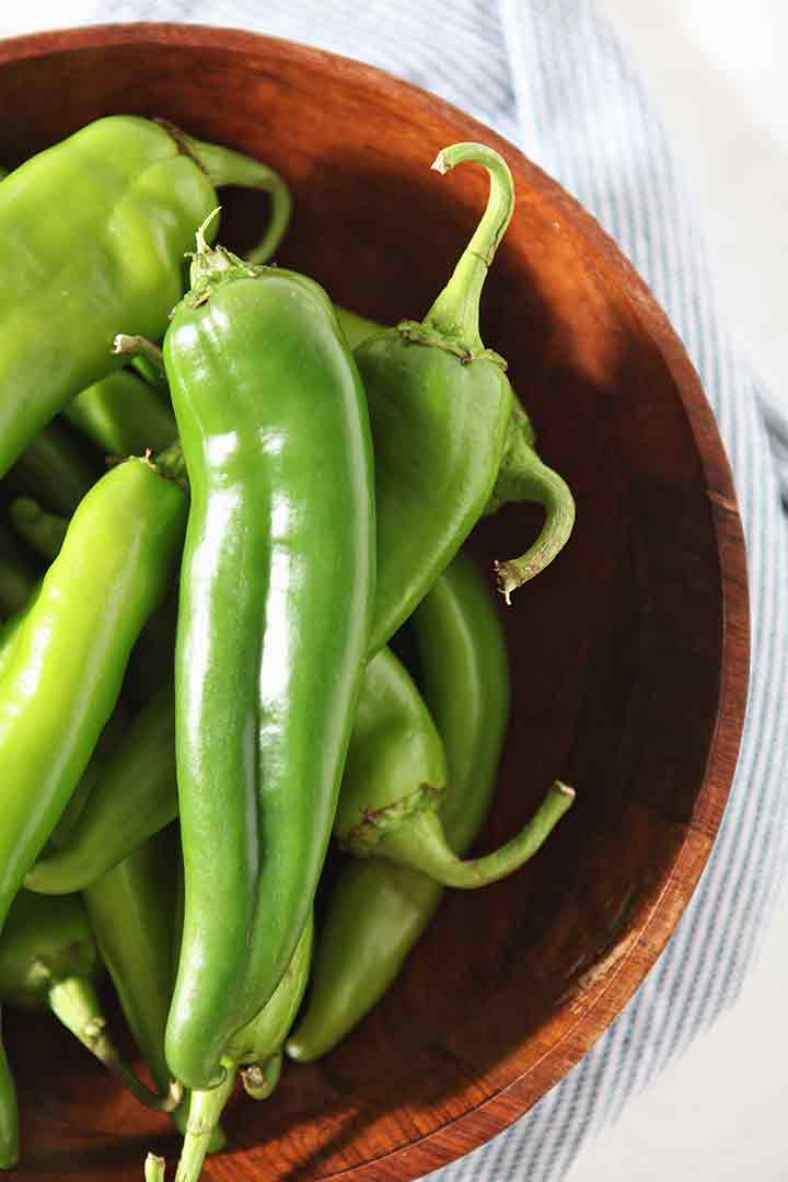 Green chiles are shown in a wooden bowl