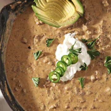 Close up of the homemade queso in a skillet with its garnishes