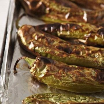 Roasted Hatch chiles line a baking dish, close up