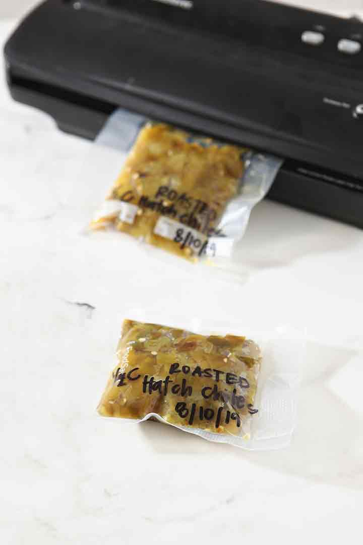 A vacuum sealer is used to seal baggies of roasted, chopped peppers for the freezer