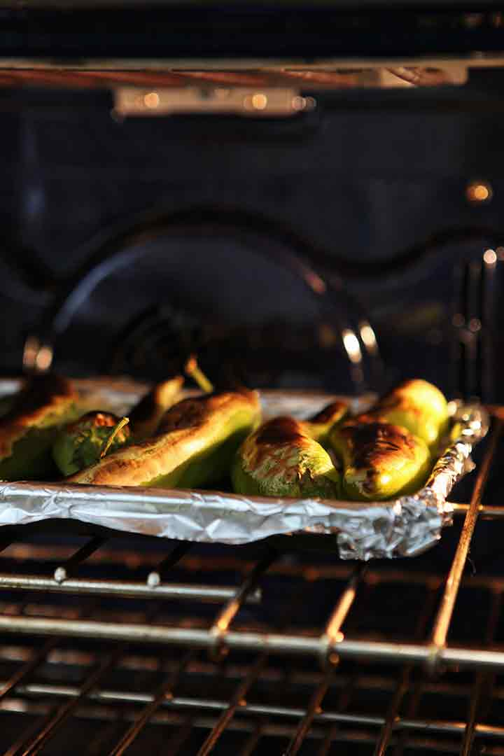 Blistered Hatch chiles on a baking sheet, under the broiler in the oven
