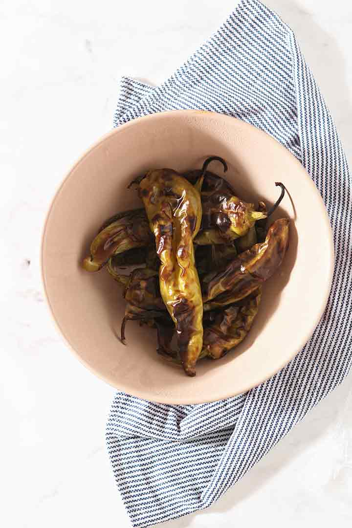 Roasted peppers are shown in a bowl, from above