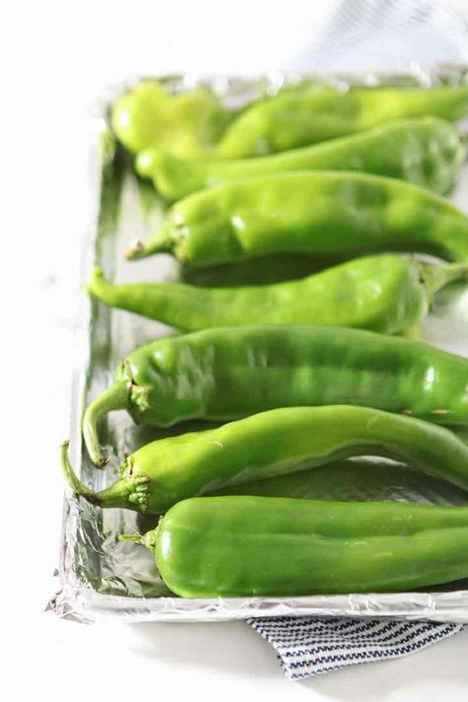 Hatch chile peppers are shown on a baking sheet, before roasting