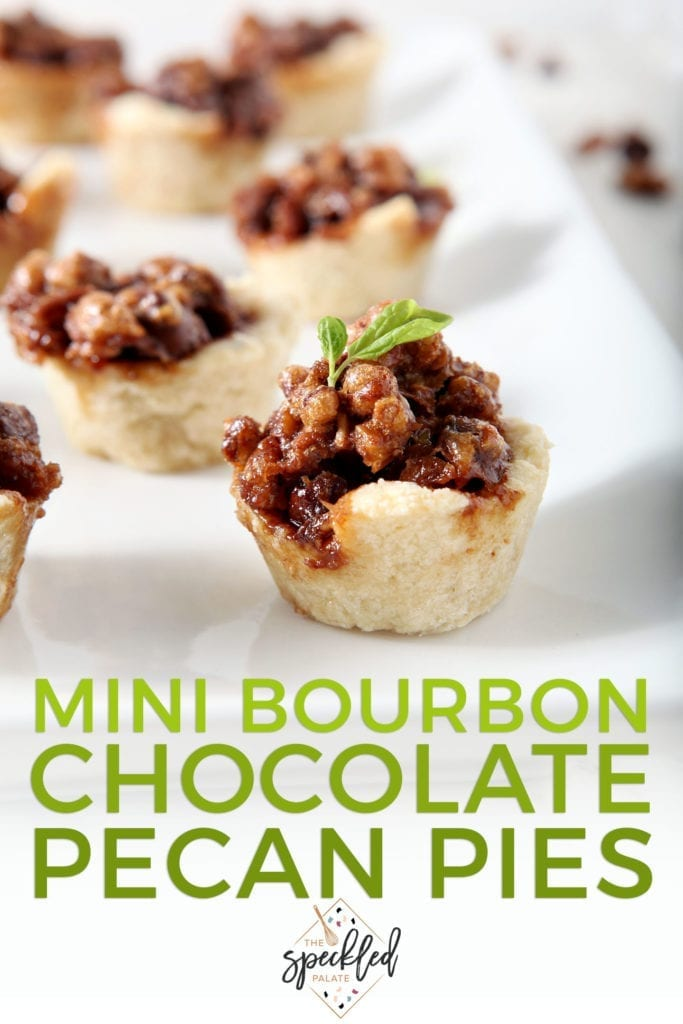 Several Mini Bourbon Chocolate Pecan Pies sit on a white platter, ready for serving