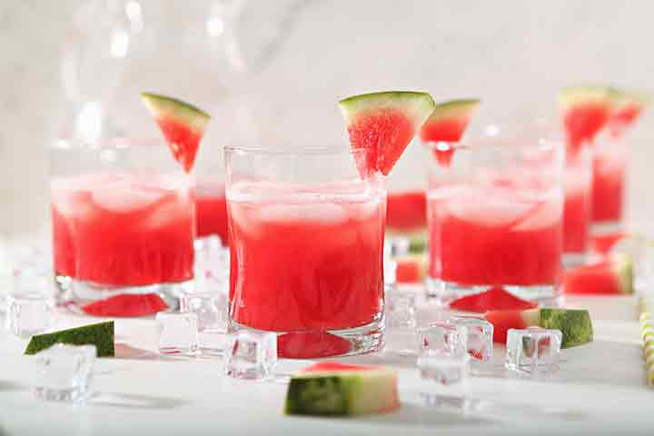 Several glasses of Watermelon Agua Fresca are garnished with watermelon wedges before drinking