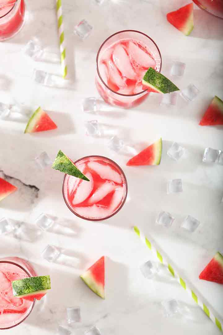 Several Watermelon Agua Frescas from above, surrounded by ice and watermelon wedges
