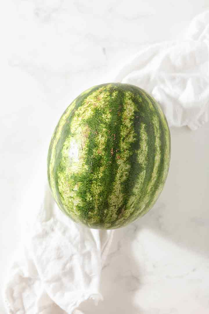 A whole watermelon sits on a marble surface, surrounded by a white tea towel
