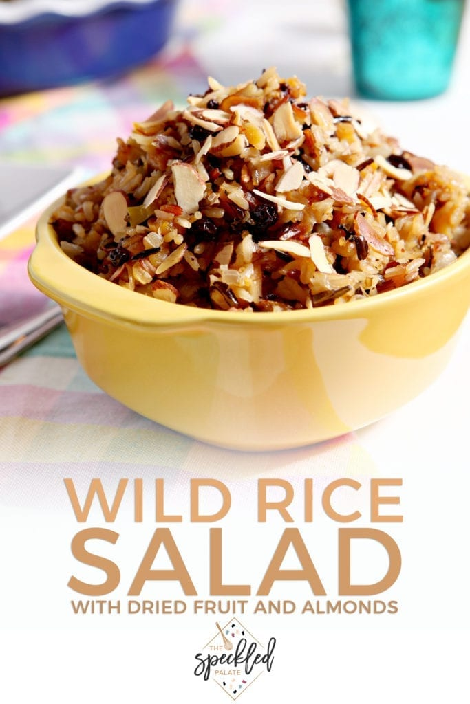 A container of Wild Rice Salad sits on a tabletop, with Pinterest text