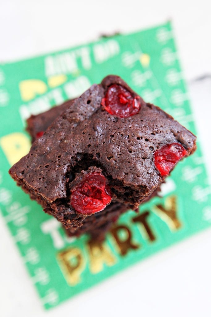 Overhead of brownies studded with cherries, from above, stacked on top of each other