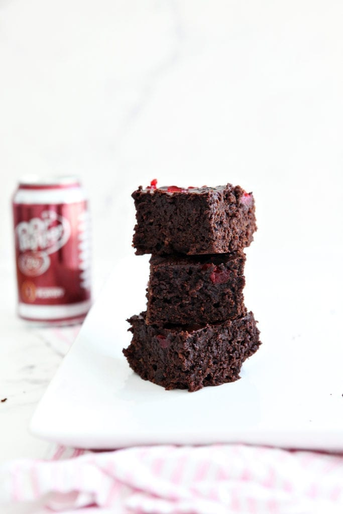 Three Dr Pepper Brownies are stacked on top of each other, before consuming