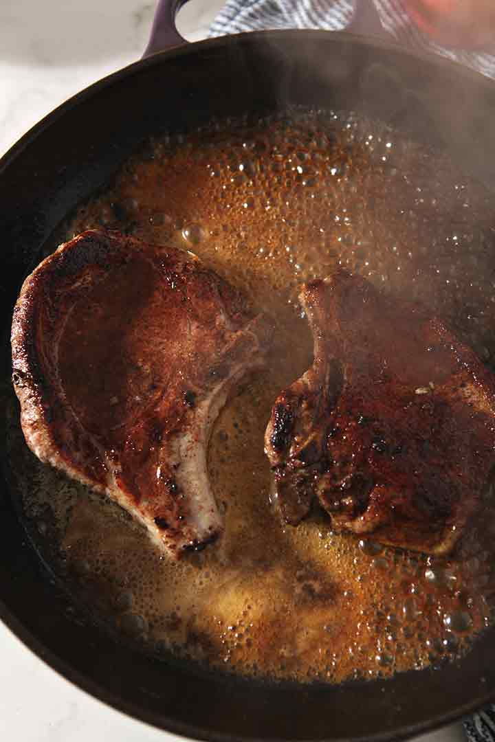 Wine cooks down in the skillet with the pork chops