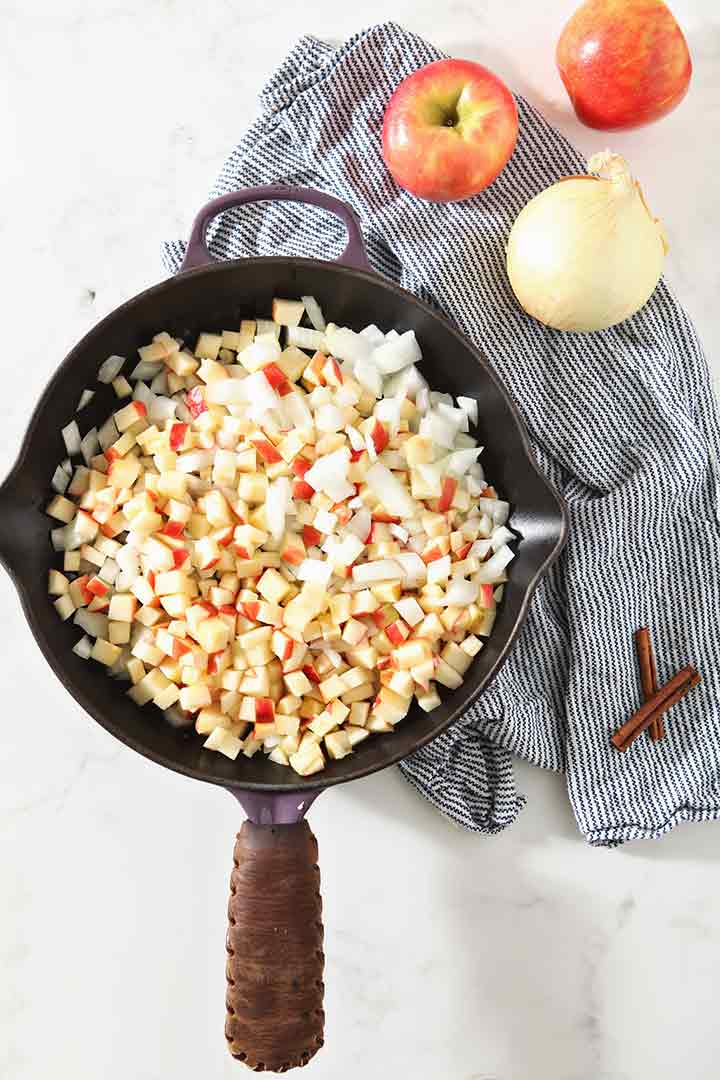 Apples and onions cook down in a cast iron skillet, from above