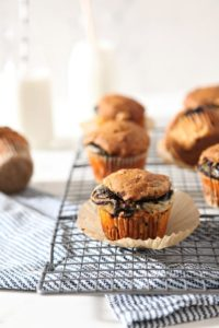 Easy Pumpkin Muffins with Cream Cheese and Nutella Swirl sit on a cooling rack with bottles of milk