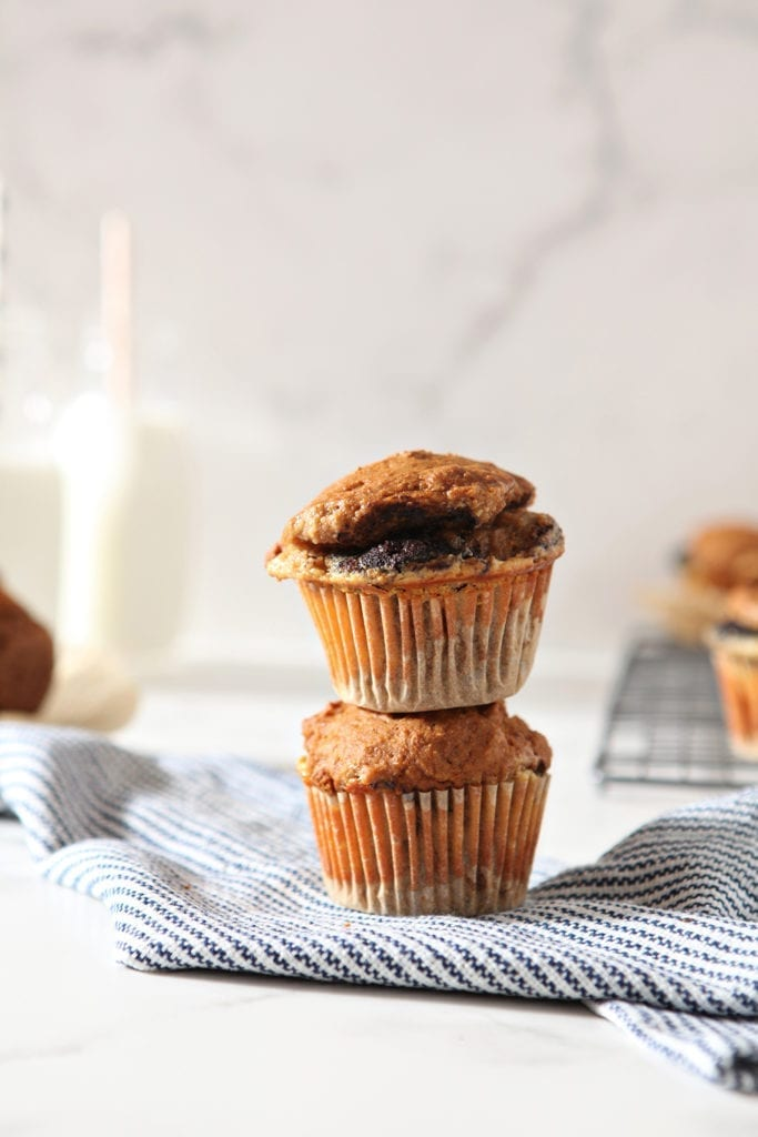 Pumpkin Muffins are stacked on top of each other, shown with glasses of milk