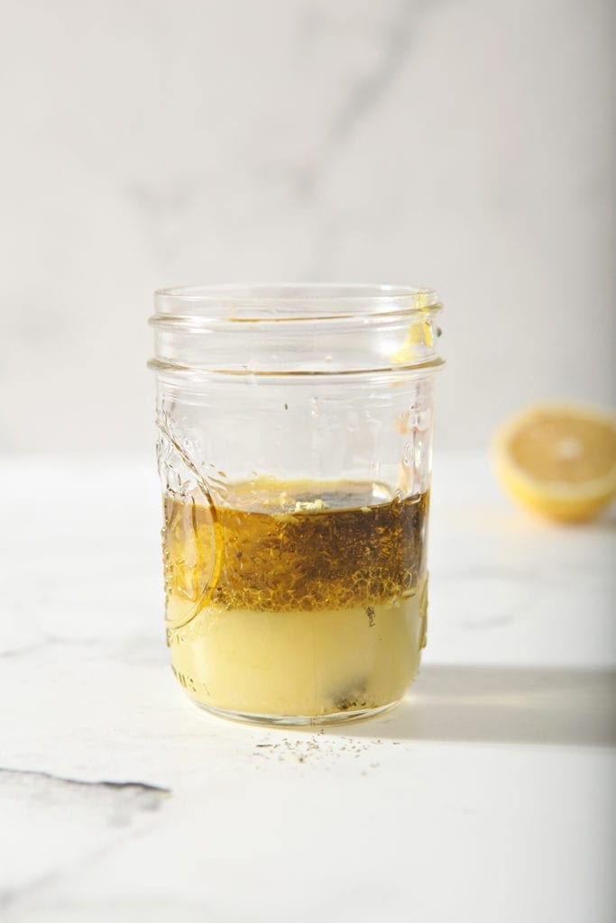 The Lemon Vinaigrette is shown, unmixed, on a marble background