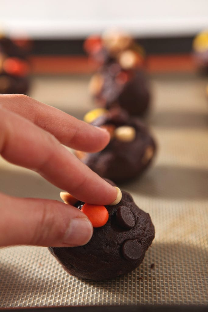 A woman presses a Reese's Pieces into a cookie before baking