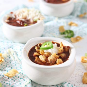 Three bowls of Homemade Texas Chili are topped with various ingredients