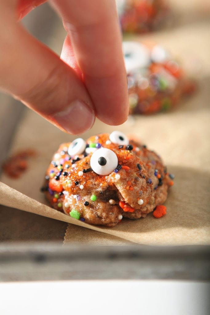 A woman presses a candy eyeball into a cookie