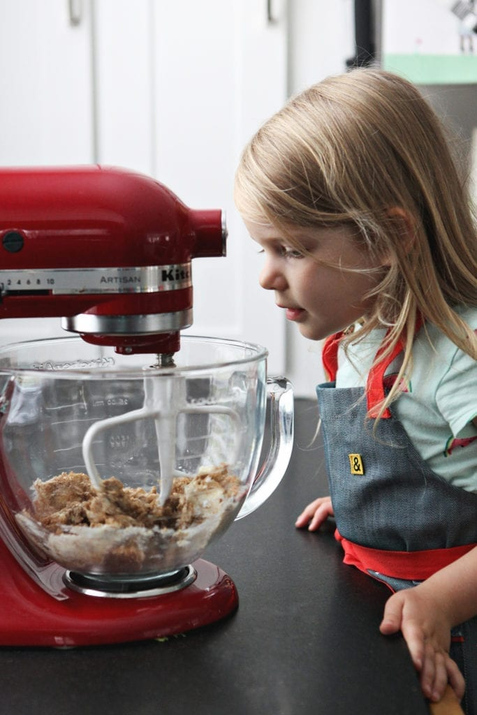 A girl watches as cookie dough ingredients mix