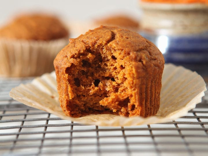 Close up of a vegan pumpkin muffin with a bite taken out of it